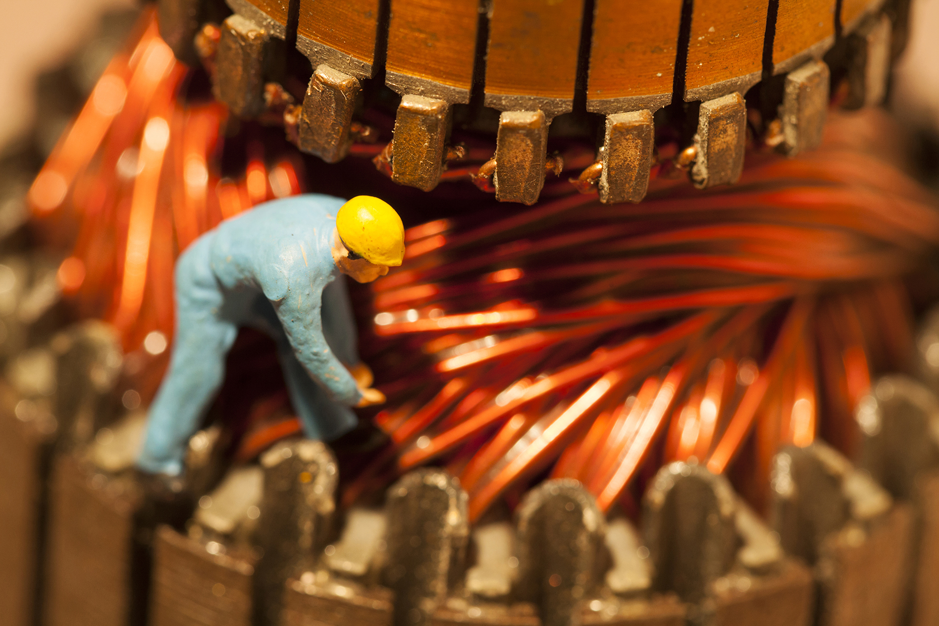 Worker inspecting large electrical mechanical part